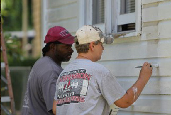 Volunteers help low-income homeowners paint their homes