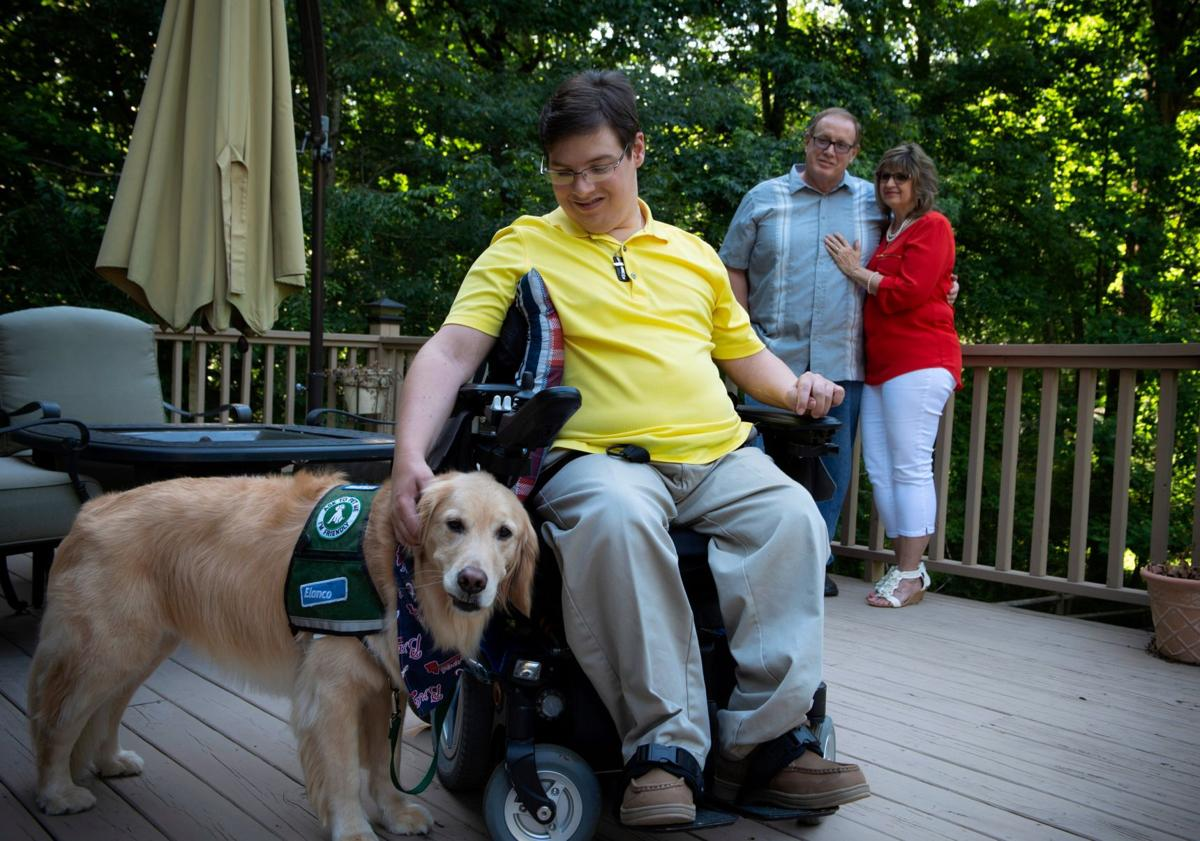 Tim Beighley with his service dog, Ringer and his parents, Doug and Angie Beighley, at their Marietta home.