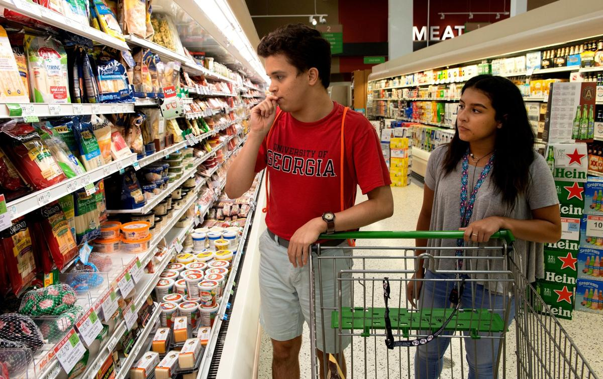 Eric Ruiz shops for cheese at a nearby Publix with Sofia Morales, a direct support professional who takes him into the community every week and helps him navigate society.
