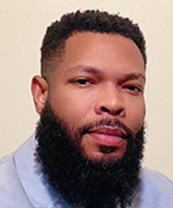 headshot of Nick Perry, a Black man with close cropped hair and a full beard looks at the camera
